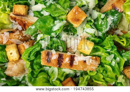 A closeup photo of a plate of chicken Caesar salad, shot from above