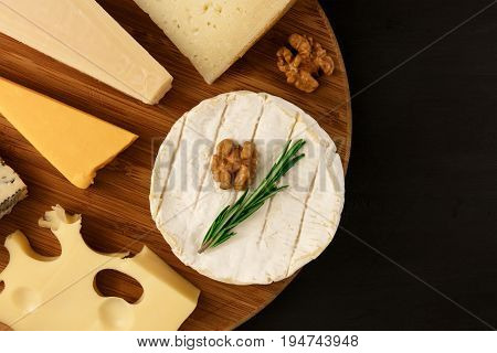 An overhead photo of a selection of cheeses, shot from above on a black texture, with a place for text