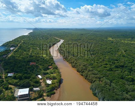 Brown river flow next to ocean aerial above view