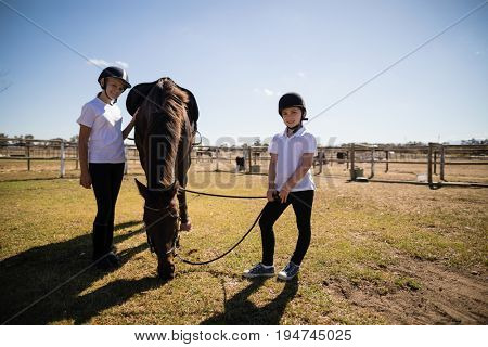 Smiling girls standing in ranch with brown house on a sunny day