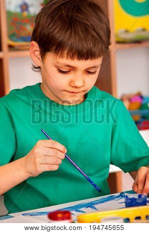 Small student boy painting in art school class. Child drawing by paints on table. Portrait boy in children's club. Craft drawing education develops creative abilities of children.