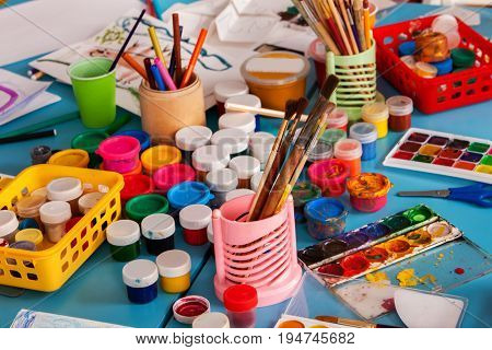 Kindergarten tables with painting brush . Preschool class waiting kids. Playroom with lot object on table. Art room for children creativity. Top view still life. Materials for creative handwork.