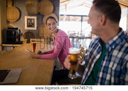 Friends interacting with each other while having glass of beer in bar