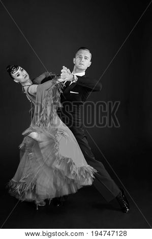 ballroom dance couple in a dance pose on black background. sensual professional dancers dancing walz tango slowfox and quickstep. black and white