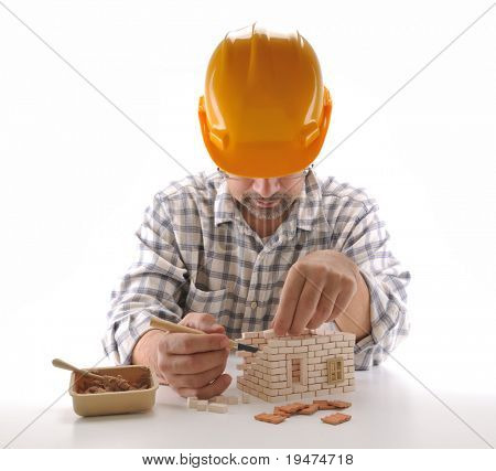 Adult man building a brick house isolated on white - a series of BUILDING A HOUSE images.