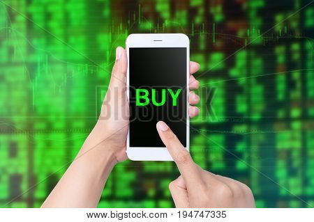 Hand Holds Smart Phone Showing Buy Over The Stock Market Chart Background