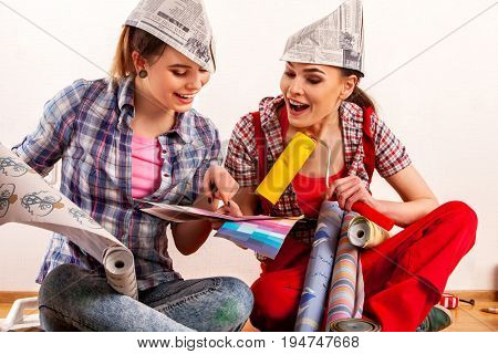 Repair home women holding painting tools roller for wallpaper. Happy girls wearing newspaper hat renovation apartment in room. It is not difficult to arrange repairs with your family idea.