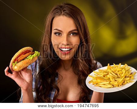 Woman eating french fries and hamburger. Portrait of student consume fast food on table. Girl trying to eat junk. Advertise fast food on daek background. Girl offers all semi-finished products.