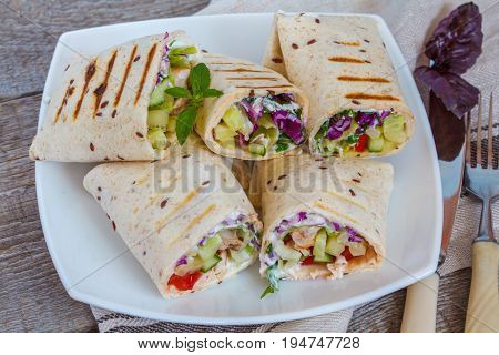 Grill chicken with fresh vegetables salad burrito wraps.