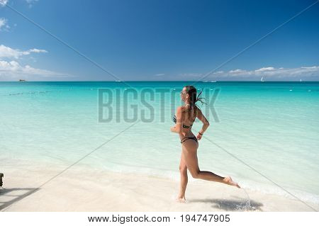 Girl in bikini running on beach with white sand turquoise sea or ocean water and blue sky on sunny day on natural environment. Sun tanning bathing. Summer vacation. Rest relaxing active leisure