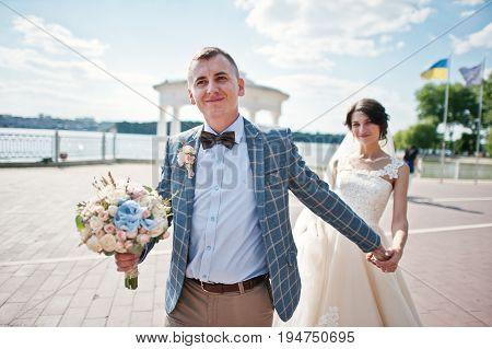 Stunning Wedding Couple Walking On Lakeside On A Sunny Day.
