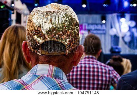Uzhgorod Ukraine - July 9 2017: Senior man in a glamorous cap with rhinestones looks concert.
