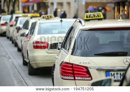 MUNICH GERMANY - MAY 9 2017 : A rear view of lined up parked taxis in the street in Munich Germany.
