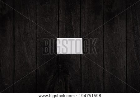 Blank corporate identity business card on black noir wood background top view template.