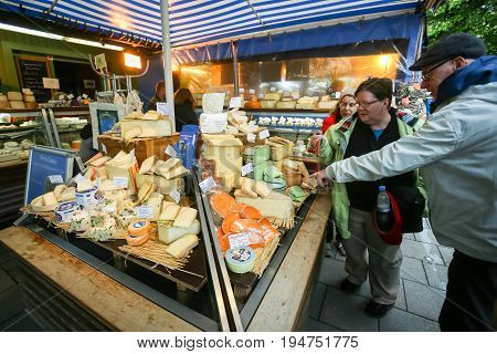 MUNICH GERMANY - MAY 9 2017 : People shopping different kinds of cheese displayed at the outdoor food market near Marienplatz in Munich Germany.