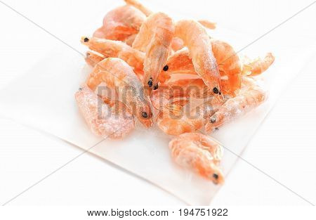 Shrimp are on the small glass dish on a white background. The horizontal frame.