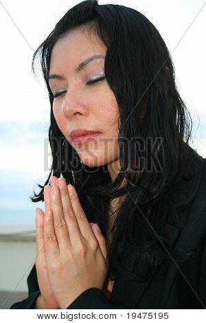 Asian business woman praying outdoors,