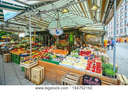 MUNICH GERMANY - MAY 9 2017 : People buying fruit and vegetable at the outdoor food market near Marienplatz in Munich Germany.