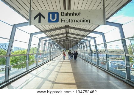 MUNCHEN GERMANY - MAY 9 2017 : People in the glass tunnel leading to the Frottmaning train station on the U6 subway line in Munich Germany. About 350 million passengers ride the U-Bahn every year.