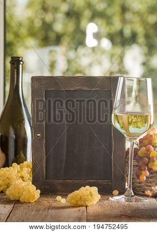 Bottle and glass of wine with grapes on wooden table