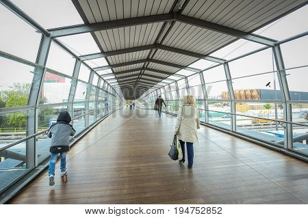 MUNCHEN GERMANY - MAY 9 2017 : People walking in the glass tunnel from the Frottmaning train station on the U6 subway line in Munich Germany. About 350 million passengers ride the U-Bahn every year.
