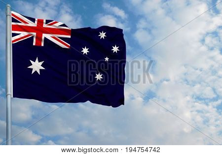 National flag of Australia on a flagpole in front of blue sky.