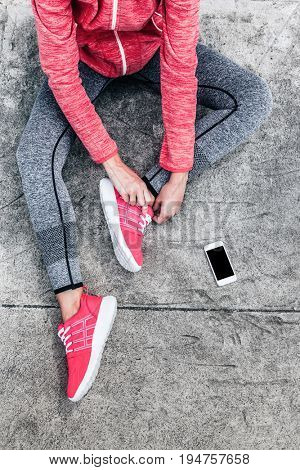 Fitness sport woman in fashion sportswear doing yoga fitness exercise in the city street over gray concrete background. Outdoor sports clothing and shoes, urban style. Tie sneakers, top view.