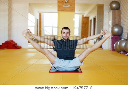 Young Male Trainer Doing Yoga Exercise In Gym