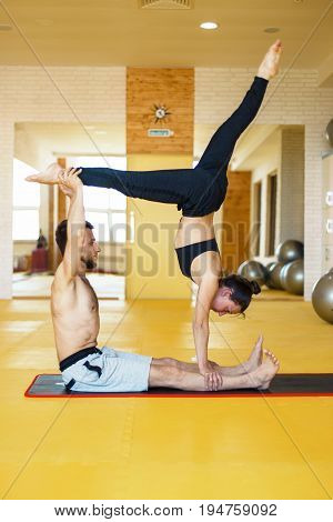 Young Man And Woman Doing Yoga In Pair Indoors. Couple Doing Acro Yoga In The Gym.
