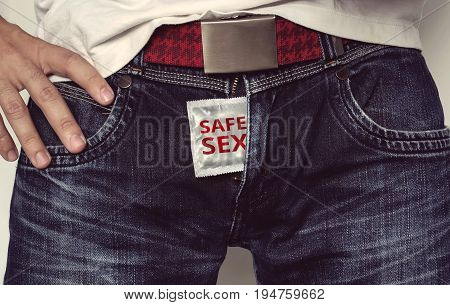 A man hold the condom a sign of a safety sex. the inscription on the condom safe sex. condom in jeans between her legs.