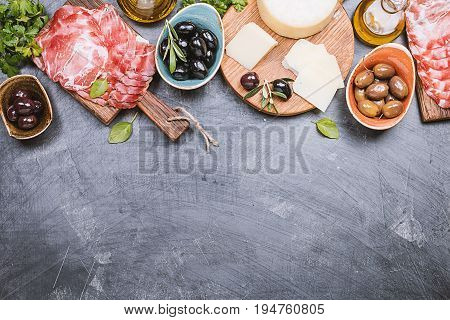 Typical italian antipasto, wooden cutting board with prosciutto, ham, cheese and olives on black background. Top view with copy space