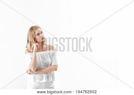 Beautiful blond woman in a white blouse and pants on a white background. copy spase
