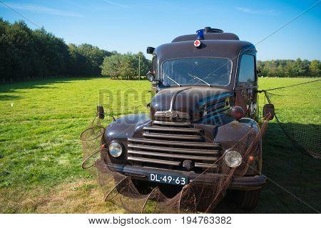 DENEKAMP NETHERLANDS - SEPTEMBER 25 2016: Vintage Ford koeln ambulance truck decorated with fishing nets