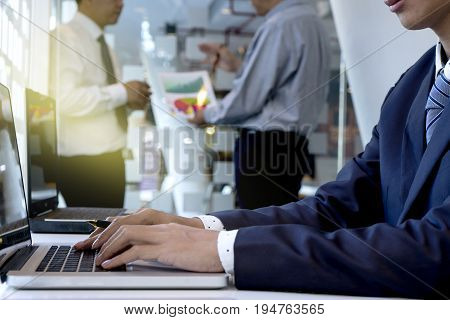 computer laptop man business using businessman office hands businessman working in his offcie hand on computer laptop and another team work talking in background