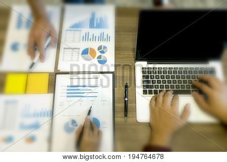 Business Man Make A Maketing Plan And Analysis Graph Paper On Wood Table