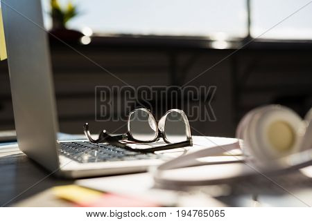 Close up of laptop with eyeglasses by headphones on table at office