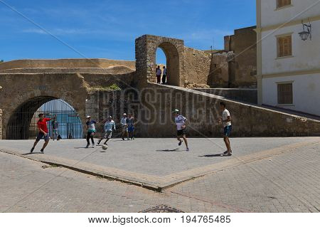 El Jadida Morocco - April 16 2016: Young man playing soccer in a square close to the walls of the fortress of the Portuguese City (Cite Portugaise) in the town of El Jadida in the Atlantic Coast of Morocco.