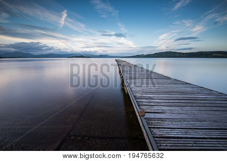 Jetty stretching out into a tranquil Loch Lomond