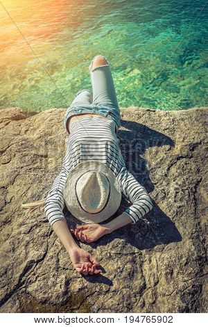 Blonde woman in summer hat resting on the edge of the rock by the sea beach. Sea view. Freedom. Wind. Summer. Beach. Vacation. Looking to a sky and sea.