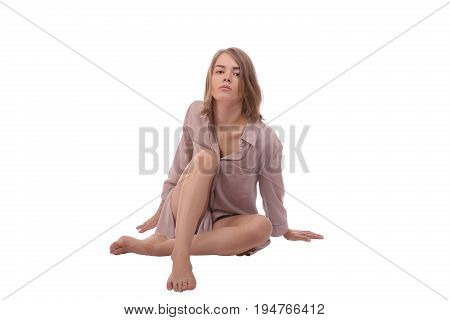 Saxy woman with blonde hair wearing in shirt sitting on the ground. isolated on white background.
