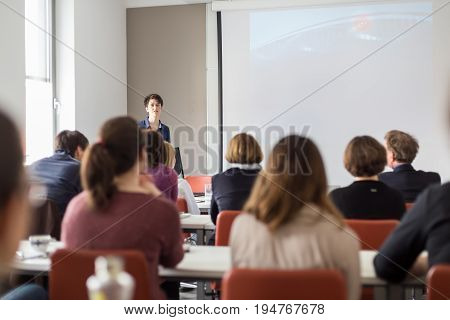 Female speaker giving presentation in lecture hall at university workshop . Participants listening to lecture and making notes. Scientific conference event.