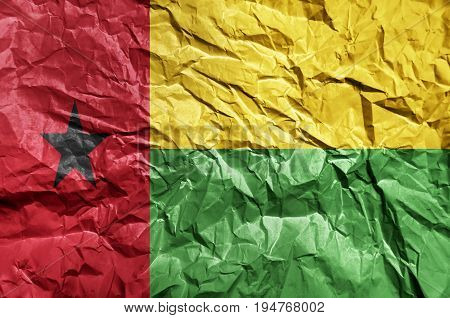Guinea Bissau flag painted on crumpled paper background
