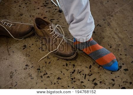 Low section of man wearing sock on floor at office