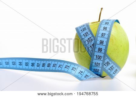 Long tape for measuring in blue colour wrapped around fresh green apple isolated on white background copy space. Concept of diet and vegetarianism