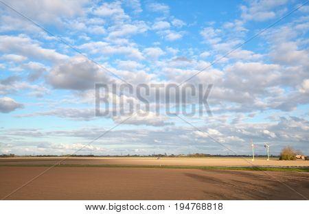 beautiful sky over plowed field in Dutch farmland