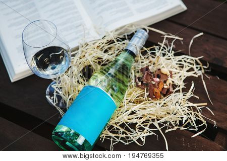 Glasswine with white wine, bottle and pieces of chocolate lies on sawdust near big open book, romantic background with expensive alcoholic drink
