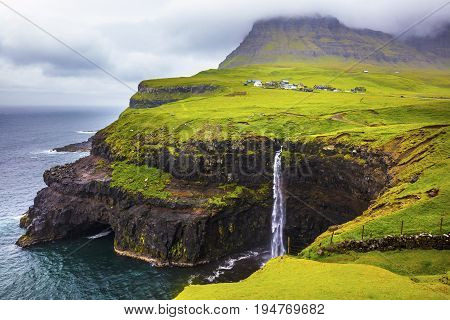 Dramatic waterfall on Faroe Islands and the village Gasadalur in the background. Rainy day in july.