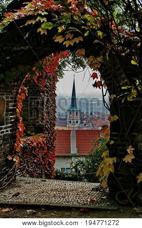 PRAGUE - CZECH REPUBLIC - OCTOBER 2010: Beautiful view of an old building with a spire through an arch with colored autumn leaves. Multicolored colors of autumn and old Prague, vertical photo