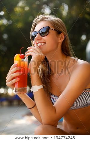 Portrait of young woman with cocktail glass chilling in the sun near swimming pool on a deck chair with palm trees behind. Vacation concept.