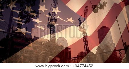 Close up of the us flag against low angle view of cranes by buildings